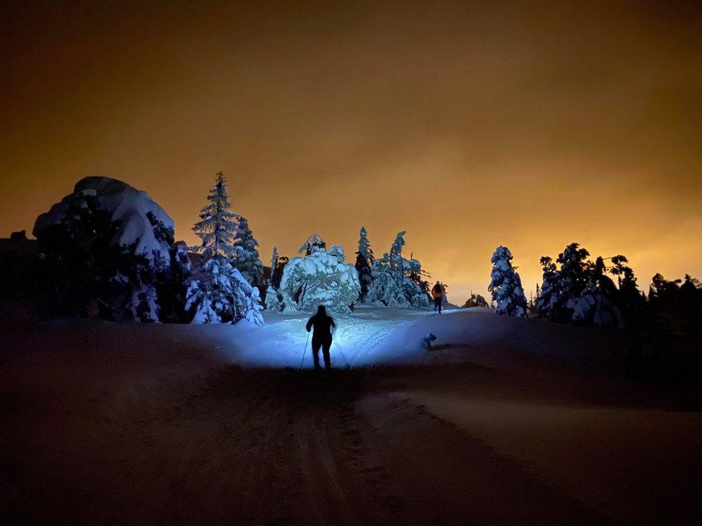 Menneske på ski- og hodelykttur. Foto.