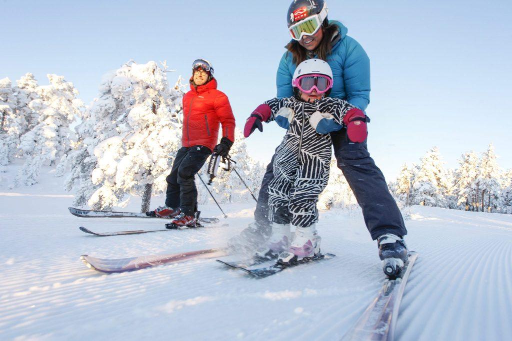 Familie står på slalom. Foto.