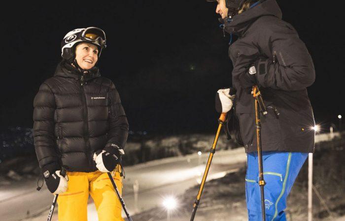 Kvinne og mann står i skibakke. Foto.